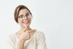 Junges schönes Mädchen im lächelnden Blinzeln der Gläser, Kamera betrachtend Finger in der Seite über weißem Hintergrund zeigend Stockfotos