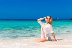 Junges schönes Mädchen im nassen weißen Hemd auf dem Strand Blaues trop Stockfotografie