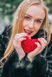 Junges schönes Mädchen im Pelzmantel, der im schneebedeckten Holz steht und hält umsponnenes rotes Herz Der Effekt von Retro-, Ko Lizenzfreie Stockfotos