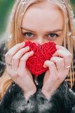 Junges schönes Mädchen im Pelzmantel, der im schneebedeckten Holz steht und hält umsponnenes rotes Herz Der Effekt von Retro-, Ko Lizenzfreie Stockfotografie