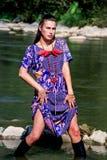 Junges schönes Mädchen im purpurroten Kleid, das im Wasser aufwirft Stockfoto