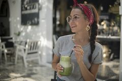 Junges schönes Mädchen im T-Shirt und in den runden Gläsern hält exotisches grünes Getränk in ihren Händen, sitzt im offenen Café stockfotos