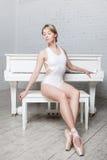 Junges schönes Mädchen im weißem Tanztrikotanzug und in Pointe-Schuhen, Balletttänzer Sitzt, Hintergrundklavier, Art, Anmut Stockfotos