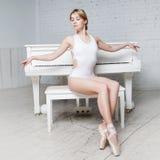 Junges schönes Mädchen im weißem Tanztrikotanzug und in Pointe-Schuhen, Balletttänzer Sitzt, Hintergrundklavier, Art, Anmut stockbild