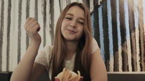 Junges schönes Mädchen isst Pommes-Frites in einem Café Rest während der Studie stock video footage