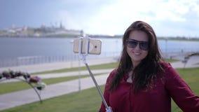 Junges schönes Mädchen macht ein Foto auf einem selfie Stock auf einem Hintergrund des Wassers, der Stadt und des Himmels HD, 192 stock footage