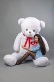 Junges schönes Mädchen mit dem glücklichen Lächeln des großen Spielzeugs des Teddybären weichen und dem Spielen auf grauem Hinter stockfotos