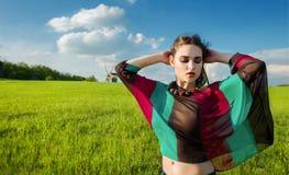 Junges schönes Mädchen mit dem langen dunklen Haar auf dem grünen Gebiet lizenzfreie stockfotografie