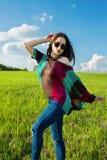 Junges schönes Mädchen mit dem langen dunklen Haar auf dem grünen Gebiet Lizenzfreies Stockfoto