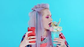 Junges schönes Mädchen mit dem purpurroten Haar tut selfie auf einem roten Smartphone stock video footage