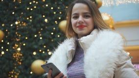 Junges schönes Mädchen mit einem Telefon in ihren Händen stock video