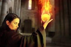 Junges schönes Mädchen mit Feuerkugel, Zauberer Lizenzfreies Stockfoto