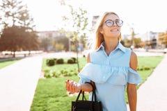 Junges schönes Mädchen mit Gläsern, Student, der in den Park schlendert stockbild