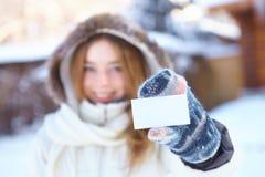 Junges schönes Mädchen mit leerer Visitenkarte. Winter. lizenzfreies stockbild