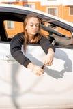 Junges schönes Mädchen schaut aus dem Autofenster, in den Händen ihrer Autoschlüssel heraus, glückliches Kaufen lizenzfreies stockfoto