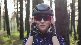 Junges schönes Mädchen setzt sich auf die Radfahrengläser, die Sturzhelm und blaues Trikot tragen Radfahrenkonzept der Straße stock video footage