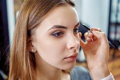 Junges, schönes Mädchen setzte an Make-up auf Augenbrauen in einen Schönheitssalon ein Stockbilder