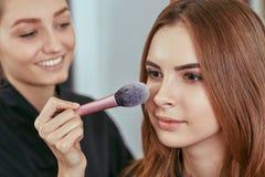 Junges, schönes Mädchen setzte an Make-up in einen Schönheitssalon ein Stockfoto