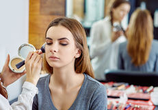 Junges, schönes Mädchen setzte an Make-up in einen Schönheitssalon ein Lizenzfreie Stockbilder