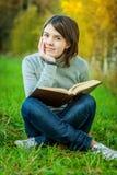 Junges schönes Mädchen sitzt auf Brücke und liest Buch Stockfotografie