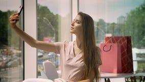 Junges schönes Mädchen sitzt im Café mit großen Fenstern in der Tageszeit und maling selfie auf Smartphone, Taschen auf Tabelle stock video footage