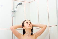 Junges schönes Mädchen steht unter der Dusche, die ihre Augen schließt und wäscht Handhaar Lizenzfreie Stockbilder