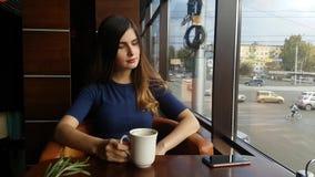 Junges schönes Mädchen, trinkender Kaffee im Café und Unterhaltung am Telefon Moderne Frau am Restaurant speist und stock video footage