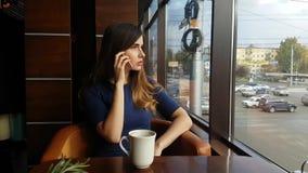 Junges schönes Mädchen, trinkender Kaffee im Café und Unterhaltung am Telefon Moderne Frau am Restaurant speist und stock video