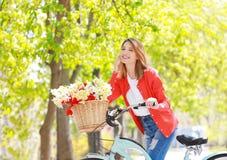 Junges schönes Mädchen und Fahrrad mit Blumen im Korb am Park Stockfotos