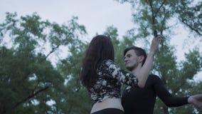 Junges schönes Mädchen und gut aussehender Mann in der schwarzen Kleidung, die Show mit der Flamme steht auf dem Riverbank durchf stock video