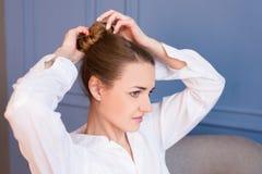 Junges schönes Mädchen in weißem men's Hemd, das ihr braunes Haar im Brötchen herstellt lizenzfreies stockfoto