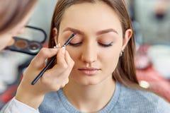 Junges, schönes Mädchen wenden Make-up auf Augenbrauen in einem Schönheitssalon an stockbild