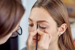 Junges, schönes Mädchen wenden Make-up auf Augenbrauen in einem Schönheitssalon an Stockfotografie