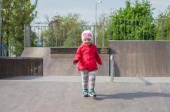 Junges schönes Mädchenbaby in einer roten Jacke und der weiße Hut, der auf dem Spielplatz im Rochen, parken, der spielt, Spaß läc Lizenzfreies Stockfoto