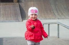 Junges schönes Mädchenbaby in einer roten Jacke und der weiße Hut, der auf dem Spielplatz im Rochen, parken, der spielt, Spaß läc Stockbild