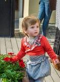 Junges schönes Mädchenkind, Kind spielend in der Straße der alten Stadt nahe den Blumenbeeten mit roten Blumen, froh und smili Lizenzfreies Stockfoto
