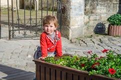 Junges schönes Mädchenkind, Kind spielend in der Straße der alten Stadt nahe den Blumenbeeten mit roten Blumen, froh und smili Lizenzfreies Stockbild
