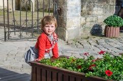 Junges schönes Mädchenkind, Kind spielend in der Straße der alten Stadt nahe den Blumenbeeten mit roten Blumen, froh und smili Stockfotografie