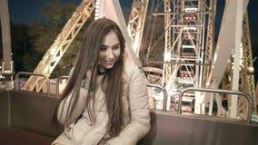 Junges schönes Mädchenmodell auf Riesenrad herein den Abend an einem Vergnügungspark, der auf einem Smartphone spricht stock video footage