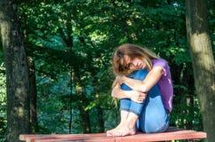 Junges schönes Mädchenmodell in den Jeans und in einem T-Shirt mit dem langen blonden Haar und traurigen dem Lächeln, die nachden Stockfoto