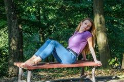 Junges schönes Mädchenmodell in den Jeans und in einem T-Shirt mit dem langen blonden Haar und traurigen dem Lächeln, die nachden Lizenzfreie Stockbilder