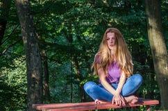 Junges schönes Mädchenmodell in den Jeans und in einem T-Shirt mit dem langen blonden Haar und traurigen dem Lächeln, die nachden Stockbilder