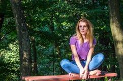 Junges schönes Mädchenmodell in den Jeans und in einem T-Shirt mit dem langen blonden Haar und traurigen dem Lächeln, die nachden Lizenzfreie Stockfotos