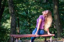 Junges schönes Mädchenmodell in den Jeans und in einem T-Shirt mit dem langen blonden Haar und traurigen dem Lächeln, die nachden Lizenzfreie Stockfotografie
