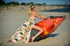 Junges schönes Mode-Modell im bunten Kleid und in der Sonnenbrille, die am Strand aufwirft Stockfoto