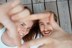 Junges schönes Paarlächeln, liegend auf den hölzernen Brettern, die Rahmen mit den Händen machen Fokus an den Gesichtern Lizenzfreie Stockfotografie