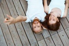Junges schönes Paarlächeln, liegend auf hölzernen Brettern Geschossen von oben Stockbilder