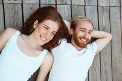 Junges schönes Paarlächeln, liegend auf hölzernen Brettern Geschossen von oben Stockbild