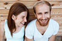 Junges schönes Paarlächeln, werfend über Hintergrund der hölzernen Bretter auf Lizenzfreie Stockfotos