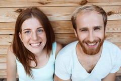 Junges schönes Paarlächeln, werfend über Hintergrund der hölzernen Bretter auf Stockfoto